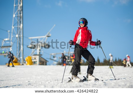 Female wearing helmet, red jacket and ski goggles standing with skis on mountain top, looking to the sun at a winter resort in sunny day with ski lifts and blue sky in background. - stock photo