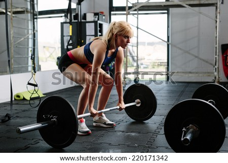 Female weightlifter preparing for a lift - stock photo