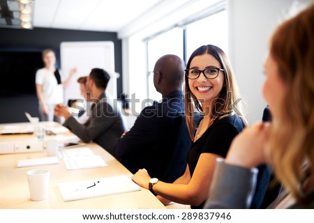 Female white executive smiling at camera during work presentation in office conference room - stock photo