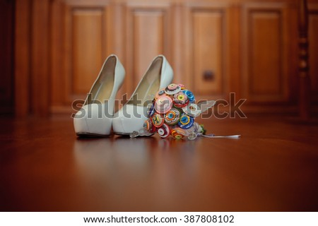 Female white wedding shoes with bride's bouquet of flowers of buttons on wooden background. - stock photo