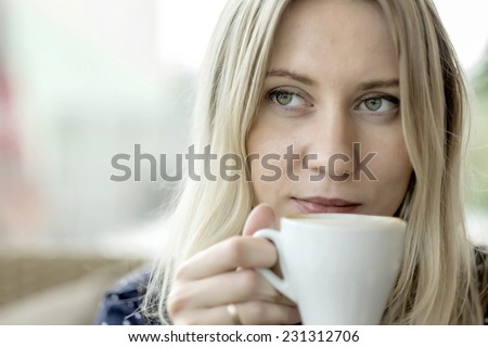 Female with coffee at cafe under sunlight - stock photo