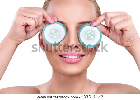female with cucumber slices over eyes - stock photo