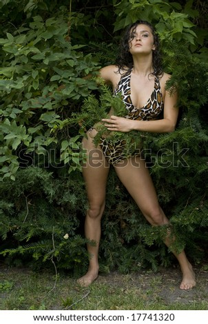 Female with dark hair posing in the bushes wearing a bathing suit - stock photo