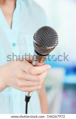 Female with microphone on room background