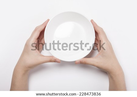 Female(woman) two hands hold a white bowl(plate)isolated white and top view.  - stock photo