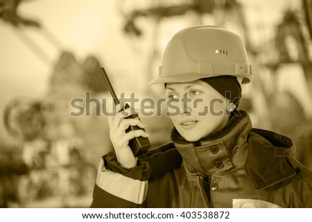Female worker in the oil field talking on the radio wearing red helmet and blue work clothes. Industrial site background.Toned sepia.