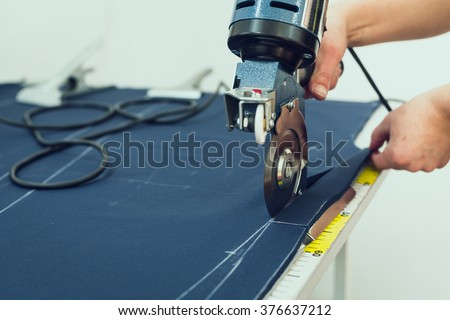 Female worker on a sewing manufacture uses electric cutting fabric machine. Sewing production line - stock photo