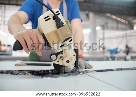 Female worker on a sewing manufacture uses electric cutting fabric machine. Sewing production line. - stock photo