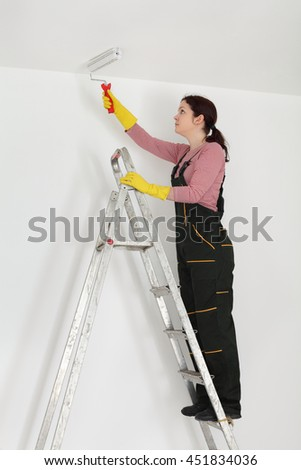 Female worker painting ceiling with paint roller from ladder - stock photo