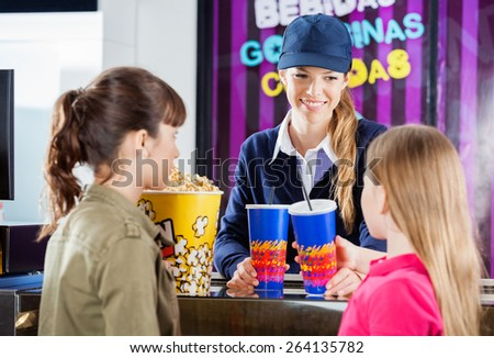 Female worker selling drinks and popcorn to girls at cinema concession counter - stock photo