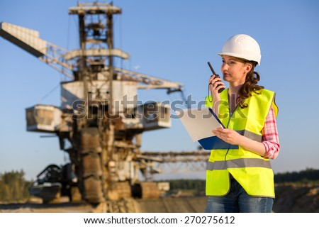 female worker talking on a radio on a background of career Stacker - stock photo