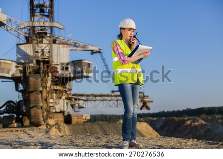 female worker talks on the walkie-talkie on a background of career Stacker