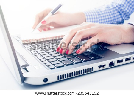 Female writing and typing on keyboard,selective focus