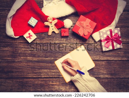 Female writing wish list in to notebook near christmas gifts - stock photo