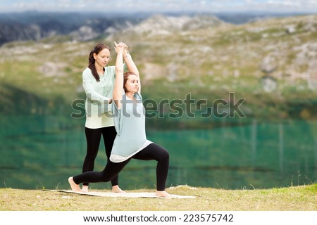 Female Yoga teacher gives assistance in training - stock photo