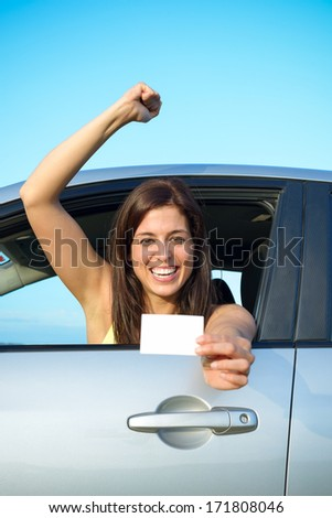Female young car driver after passing the driving license test. Successful woman showing blank card and smiling in vehicle. - stock photo