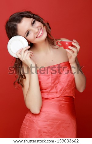 Female young woman with coffee cup/Pretty girl in red dress on the red background - stock photo