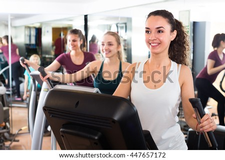 Females riding cardiovascular trainers in modern gym for women  - stock photo