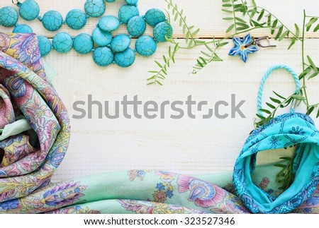 Feminine accessories framed background, empty middle space, scarf jewelry, floral romantic setting, turquoise fresh springtime colors - stock photo