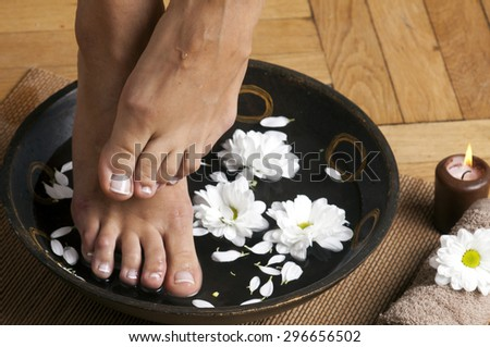 Feminine feet in foot spa bowl with flowers, towel and candle. - stock photo