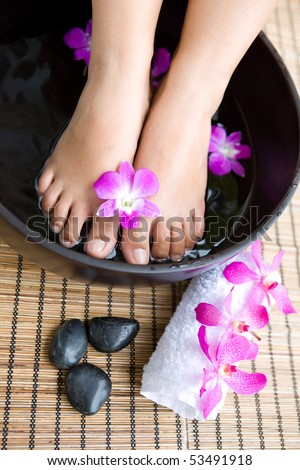 Feminine feet in foot spa bowl with orchids - stock photo