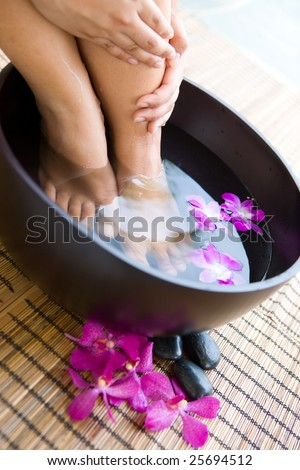 Feminine feet in oriental foot bath with flowers and pebbles