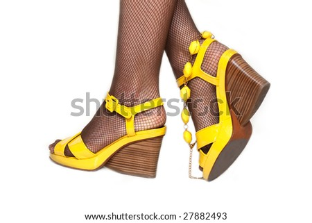 Feminine legs, yellow sandals, pantyhose in net insulated on white background - stock photo