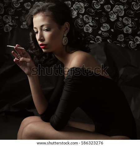 Femme fatale and Hollywood diva concept. Emotive portrait of a tired dancer smoking and posing over retro wallpaper with flowers and wrinkled black paper background. Vintage style. Studio shot - stock photo