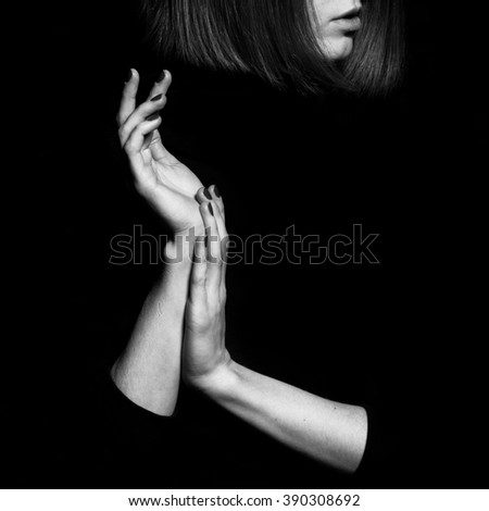 Femme fatale concept. Old classic movies actress style. Close up profile portrait of gorgeous young woman with beautiful hands over black background. Black and white studio shot - stock photo