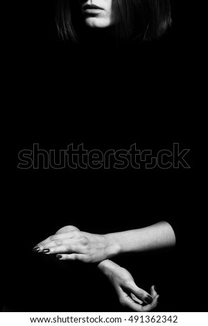 Femme fatale concept. Old classic movies actress style. Close up profile portrait of gorgeous young woman with beautiful hands over black background. Black and white studio shot. Copy-space
