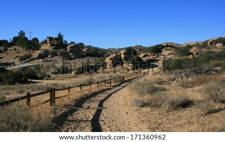 Fence bordering a recreational trail in the hills, California - stock photo