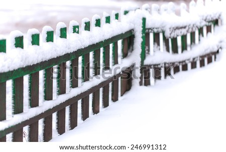 Fence covered by first snow in perspective.