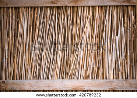 fence from the dry reed and wood - stock photo