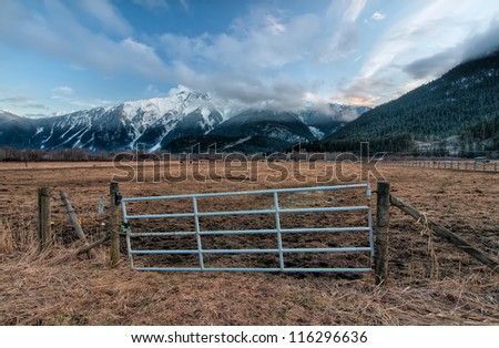 Fence gate for a farm pasture with snowy mountains in background - stock photo