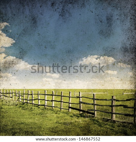 Fence in the green field under blue cloud sky. Beautiful grunge landscape background - stock photo