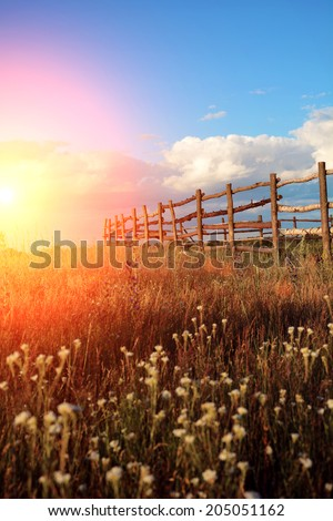 Fence in the green field under blue cloud sky. Beautiful landscape  - stock photo
