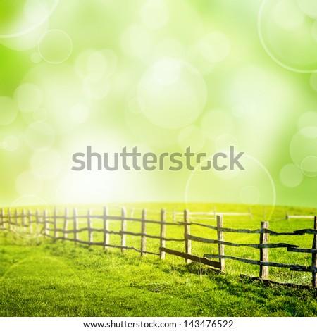 Fence in the green field under bokeh sky. Beautiful landscape - stock photo