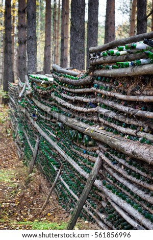 Fence made from empty green champagne bottles and logs in the forest near the Eurasian line in Russia. It is a popular wedding venue with champagne toasts to the new couples. Shallow depth of field.