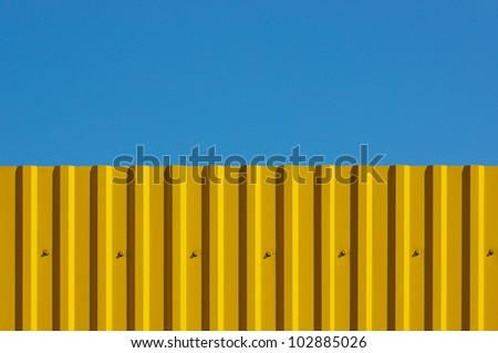 Fence made of corrugated yellow against the blue sky. It looks like a flag of Ukraine - stock photo