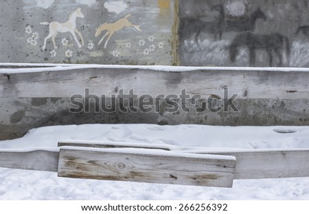 fence of a horse stable in winter covered with snow with horses painted at the grey wall background  - stock photo