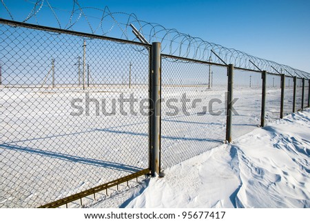 Fence with barbed wire on a background of snow - stock photo
