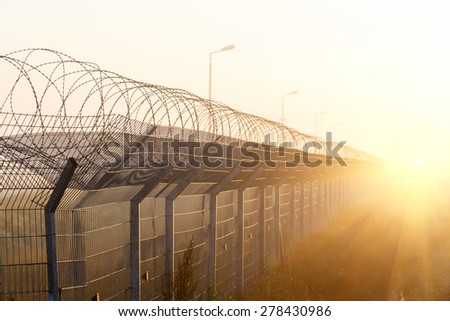 fence with barbed wire on the border of the object at dawn with fog in the summer, russia