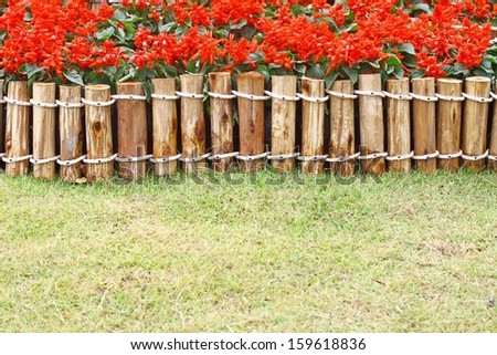 Fence with red flowers - stock photo