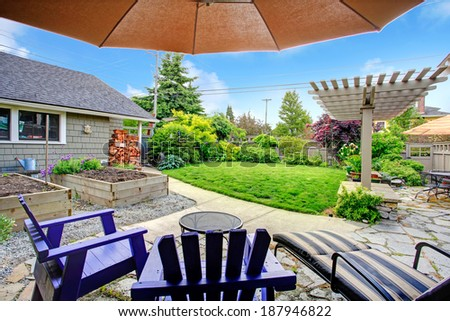 Fenced backyard with lawn, garden bed, shed with woods and pergola. View from patio area with chairs and umbrella - stock photo