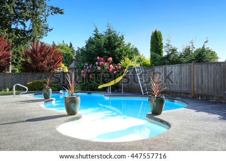 Fenced backyard with small beautiful swimming pool and playground - stock photo