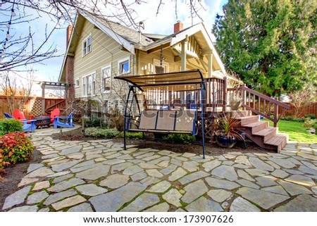 Fenced stoned backyard with flowerbed, trim, patio swing and barbecue area - stock photo