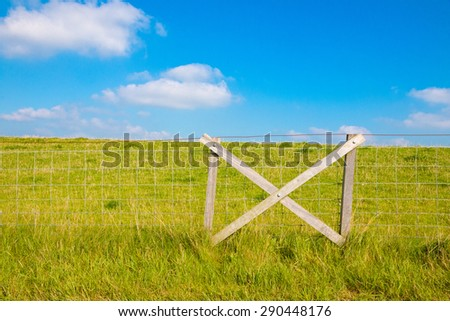 Fencing at grassy dike and blue sky with clouds - stock photo