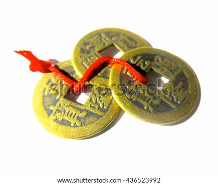 Feng Shui Wealth and Good Luck - 3 Gold Feng Shui Coins Tied with Red String Isolated Close Up - stock photo