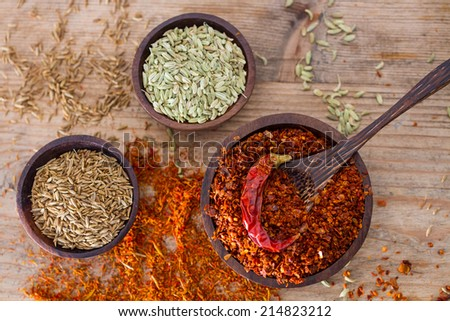 Fennel and other seeds and a wooden bowl containing chili pepper flakes.