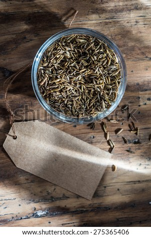 fennel seed in a bowl on wooden background with blank label next - stock photo
